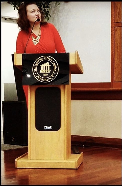 Human Services Technology instructor Amanda Faulk standing at a podium speaking at a conference