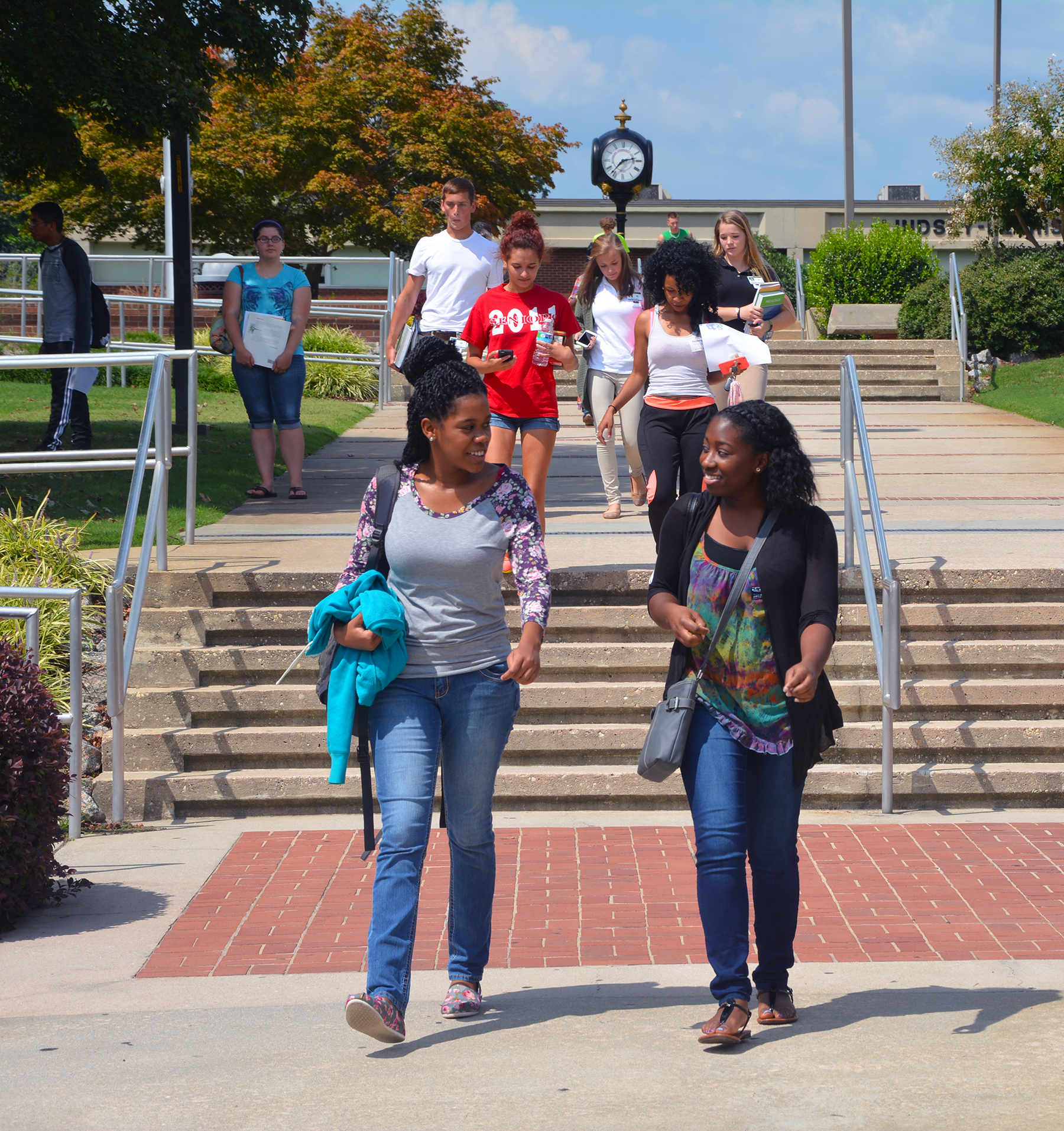 Career and College Promise high school students who are dually enrolled at Richmond Community College walk down stairs leading to the parking lot of the main campus.