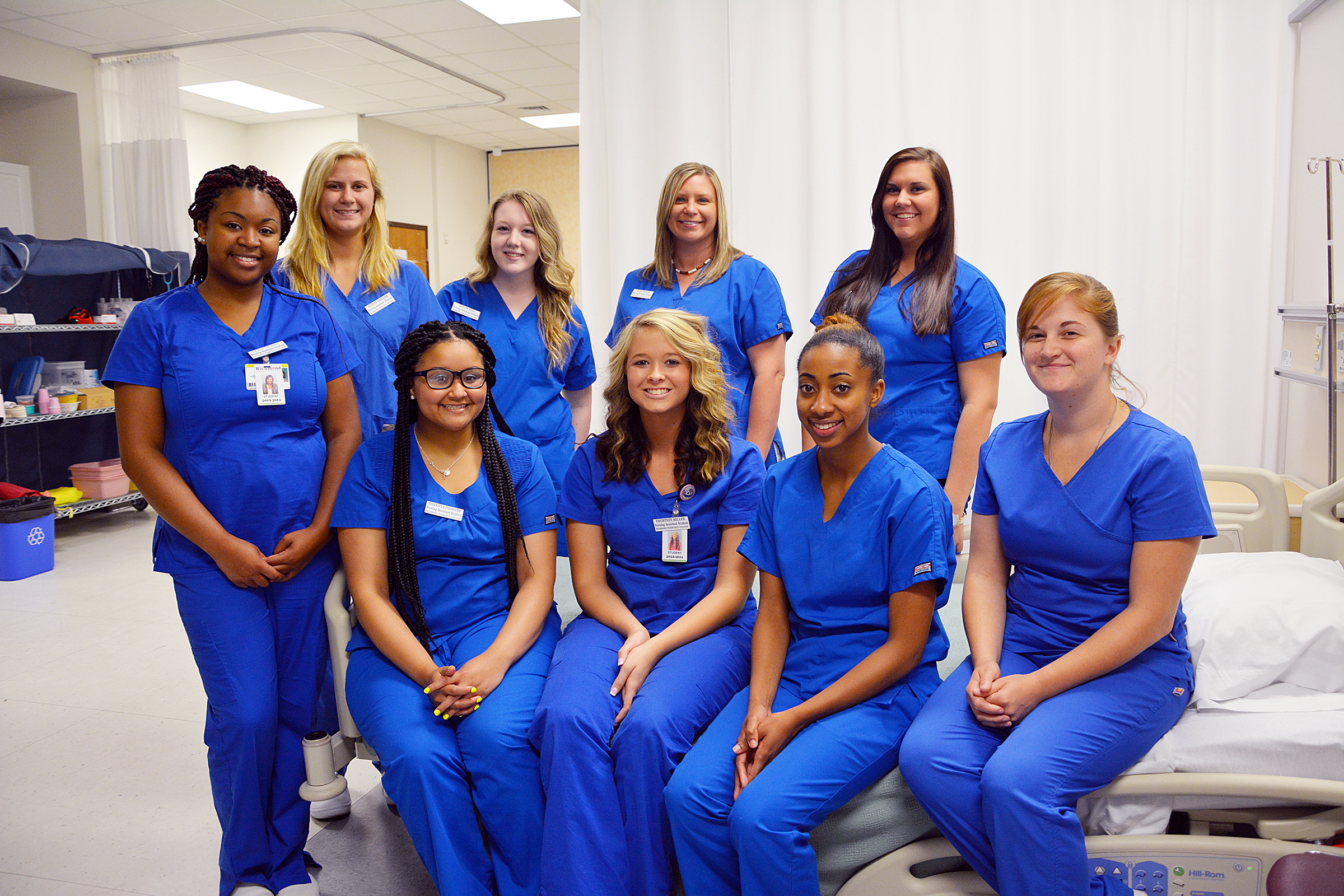 Nursing Assistant graduates pose for a photo in a nursing lab setting.