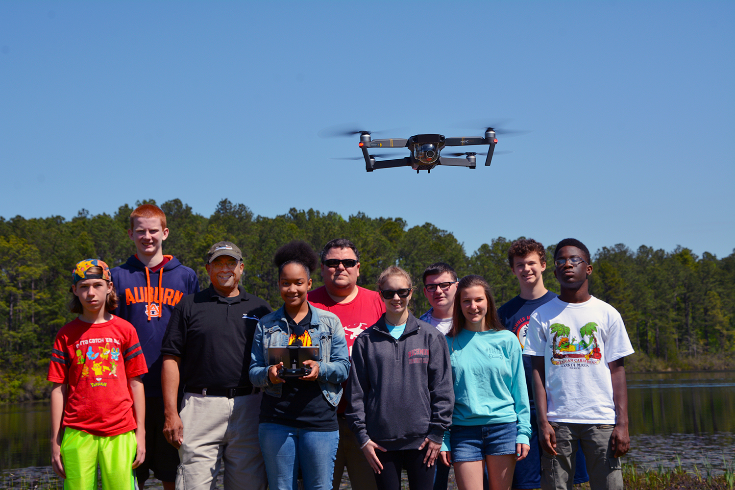 The Drone Academy students and instructors stand by the lake with a drone hovering in front of them.