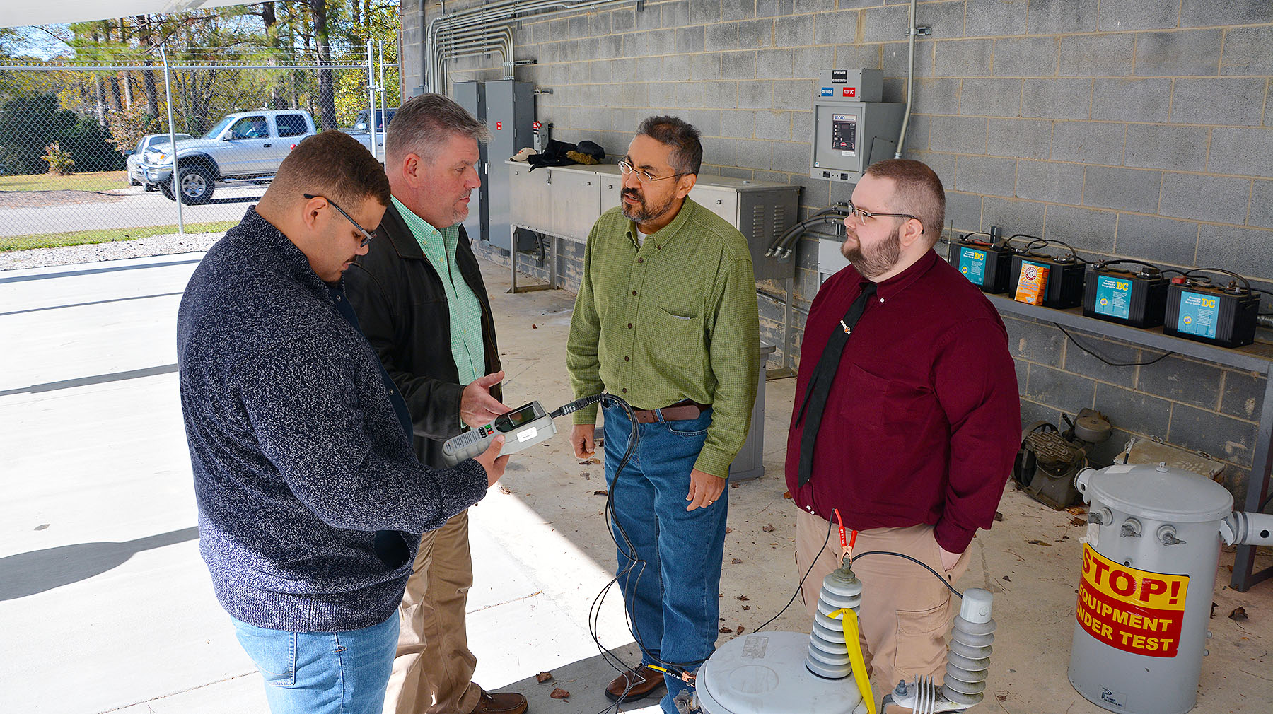 EUSRT students and instructor stand in substation with test device