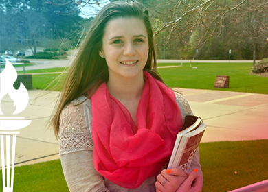 Office Administration graduate Hailey Stafford holding books on college campus