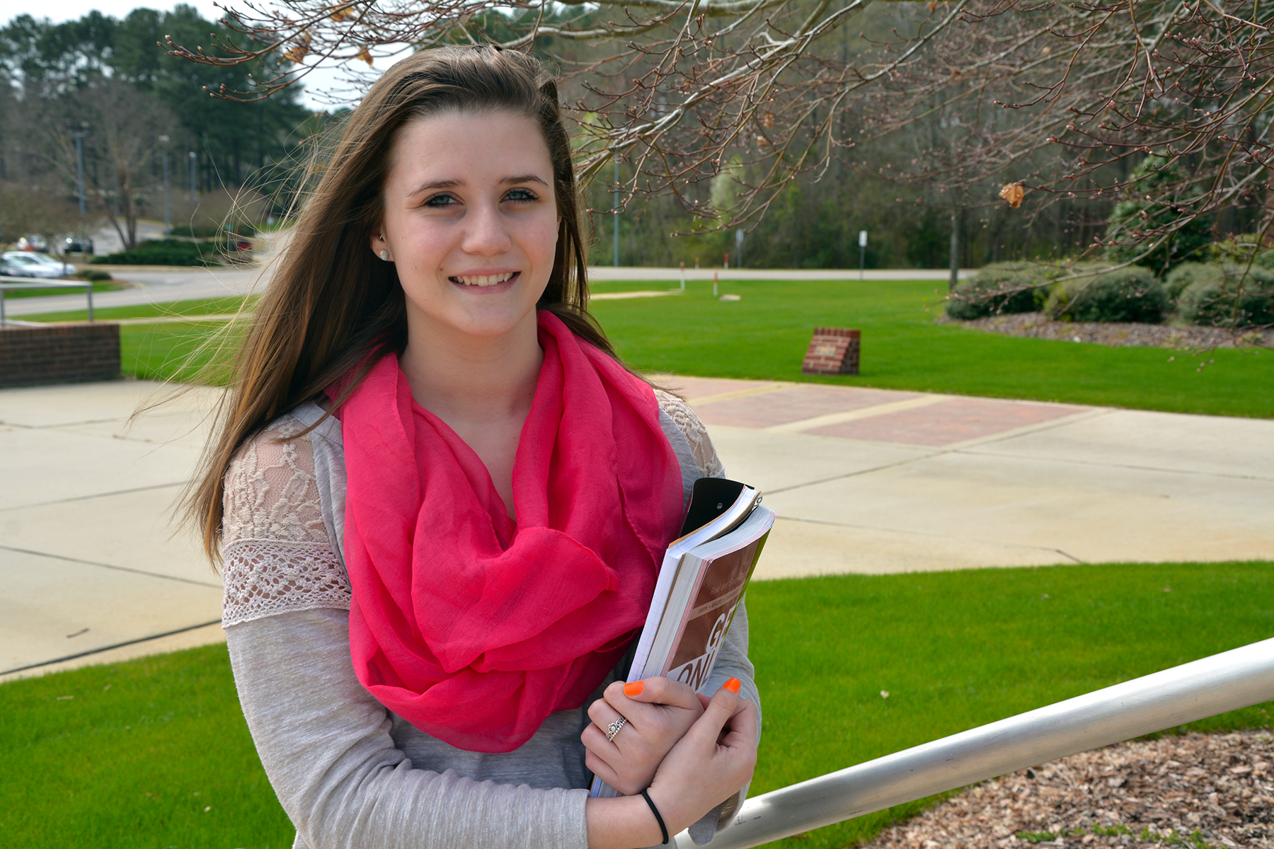 RCC graduate Hailey Stafford stands with textbooks on the main campus of RCC in Hamlet.