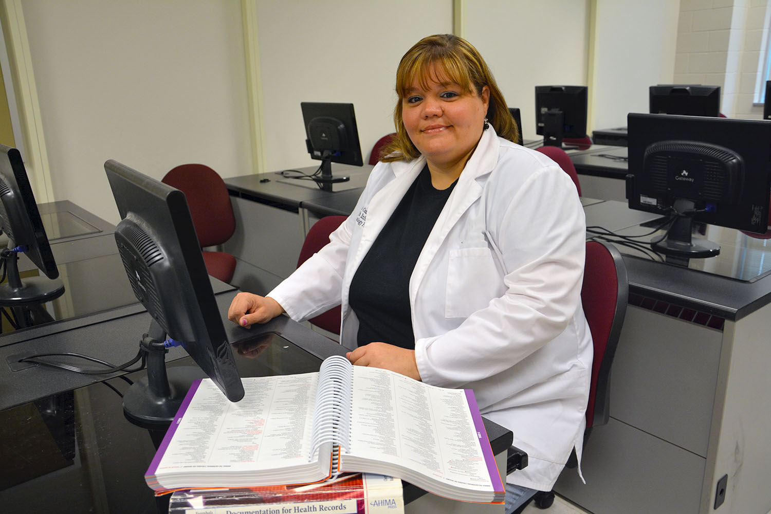 Health Information Technology student sits at a desk in a computer lab with a text book open in front of her.