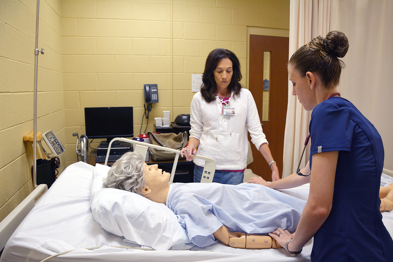 Nursing student working with an instructor and a mannequin in nursing lab
