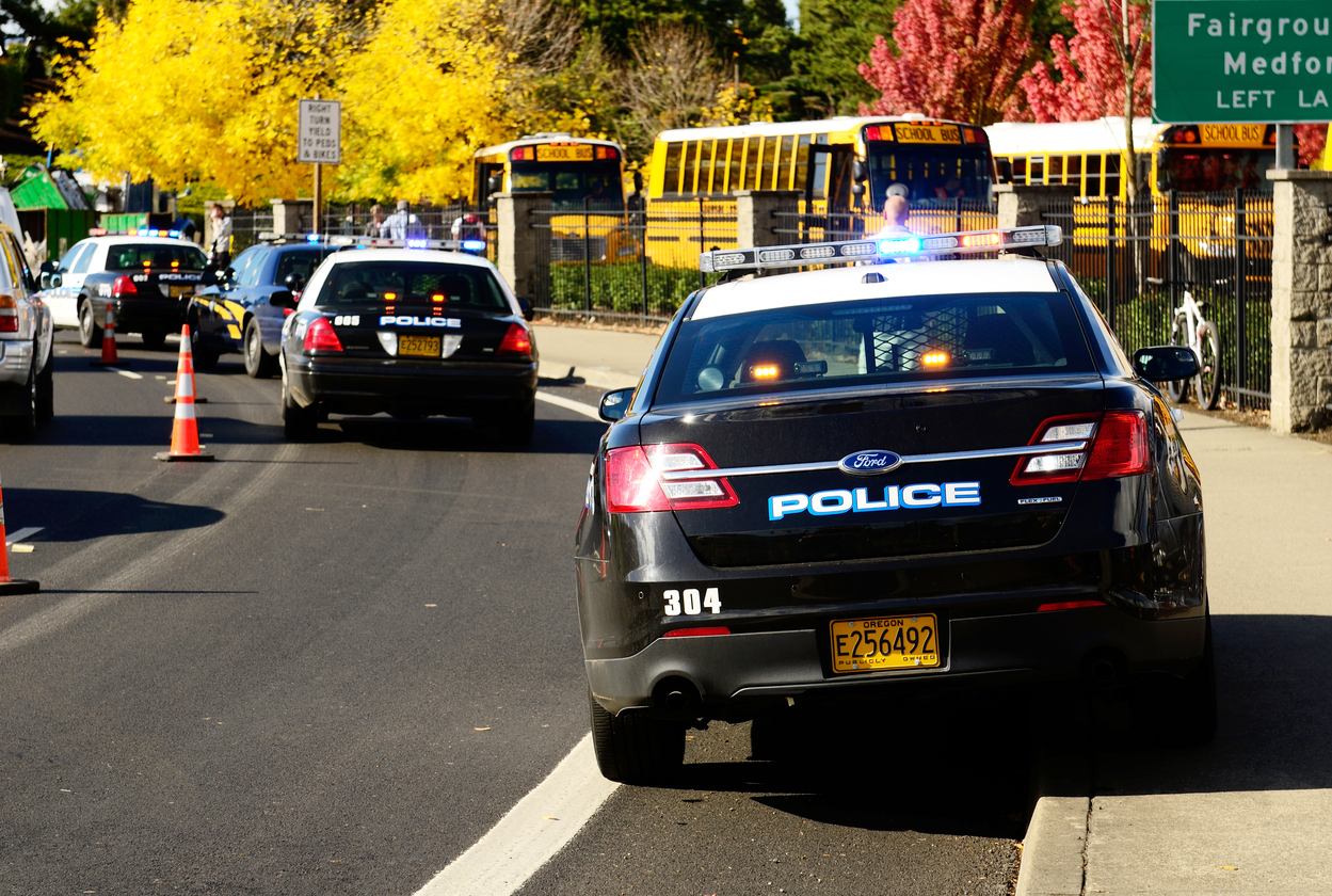 Police cars parked in front of a school