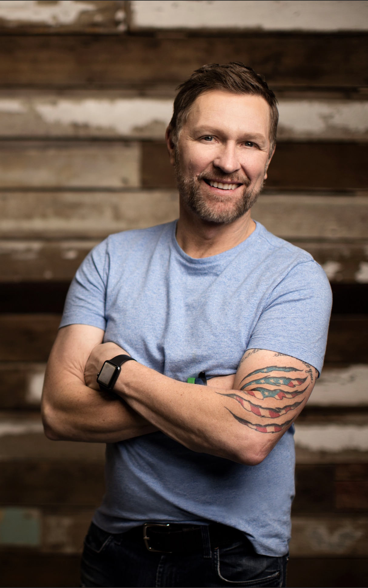 Posed picture of Craig Morgan with wood slat background.