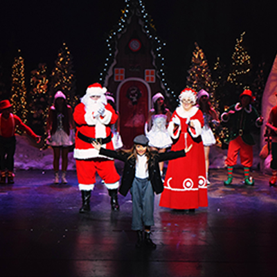 Santa and Mrs. Claus on stage with performers
