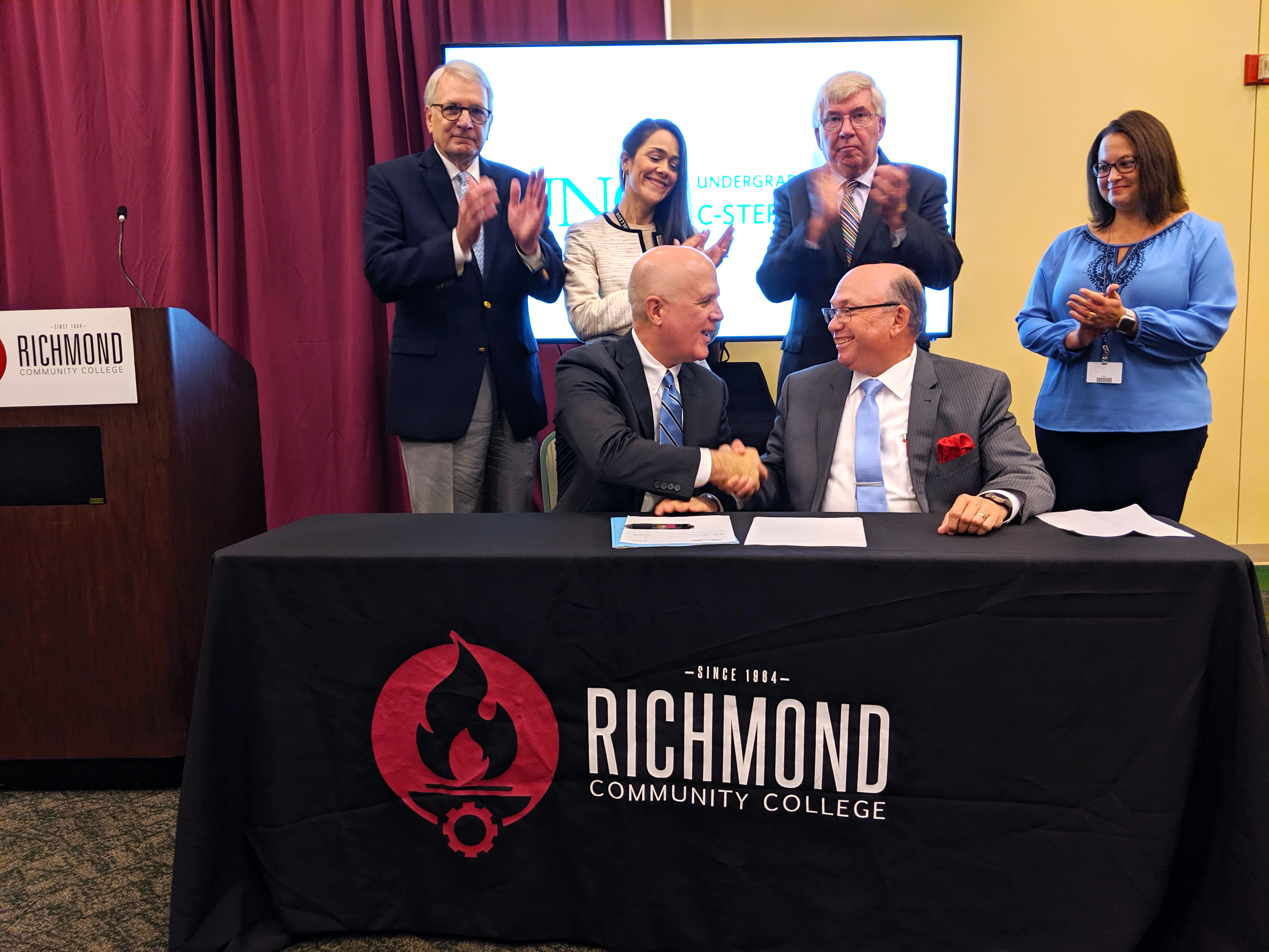 RichmondCC and UNC leaders sit at a table and sign a document while others look on.