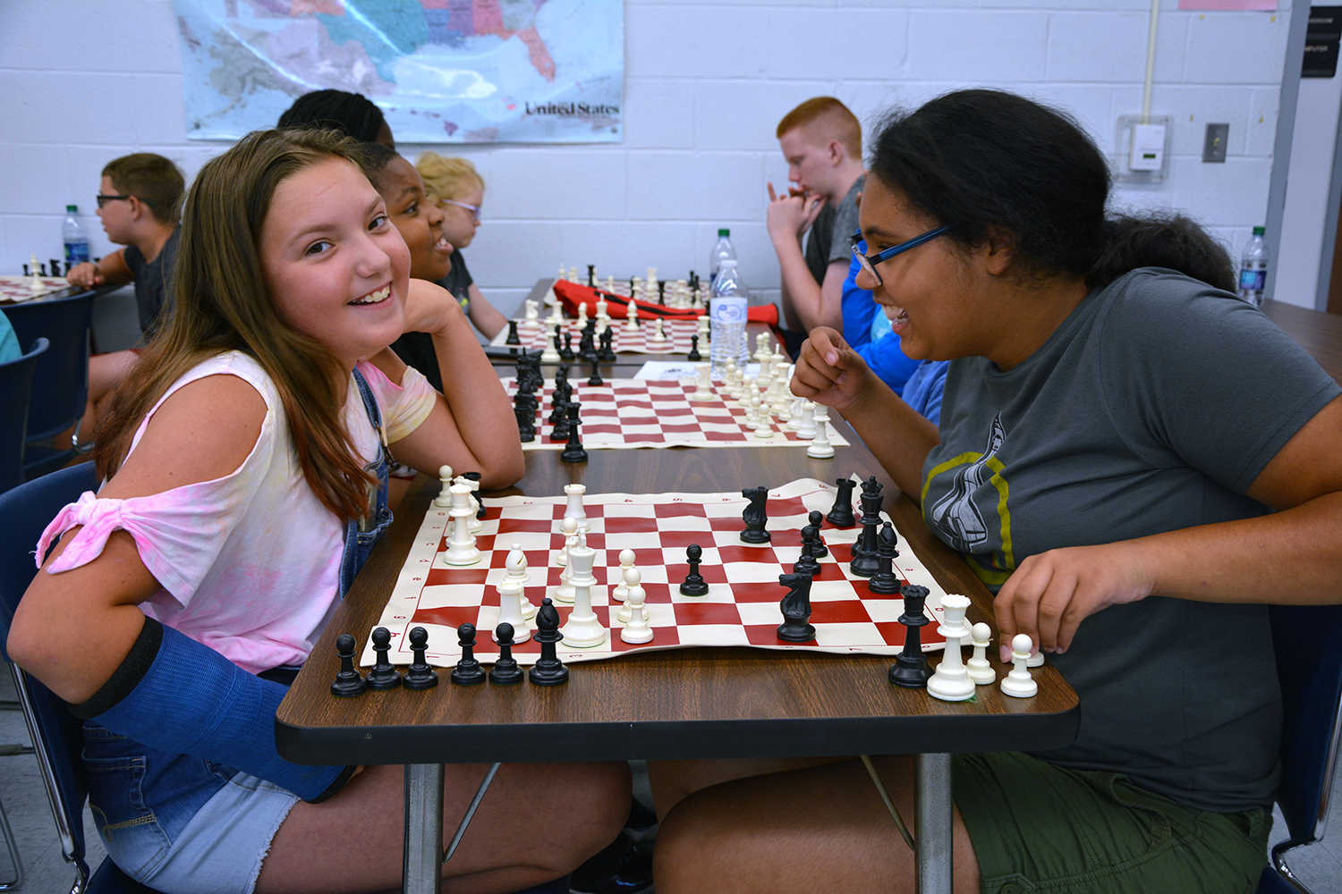 Two girls play chess at a table with other kids in the background