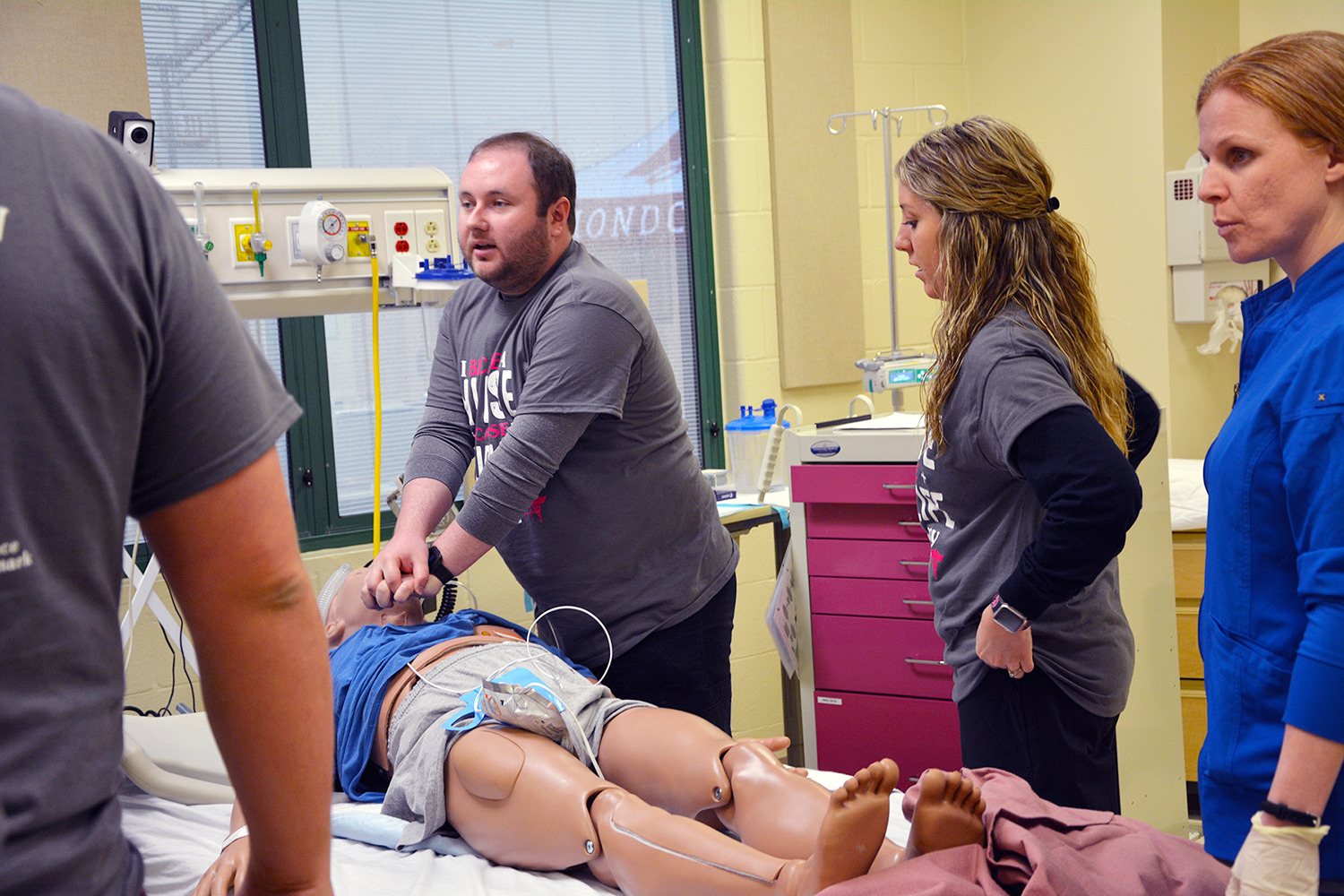 Nursing student performs chest compressions on a mannequin.