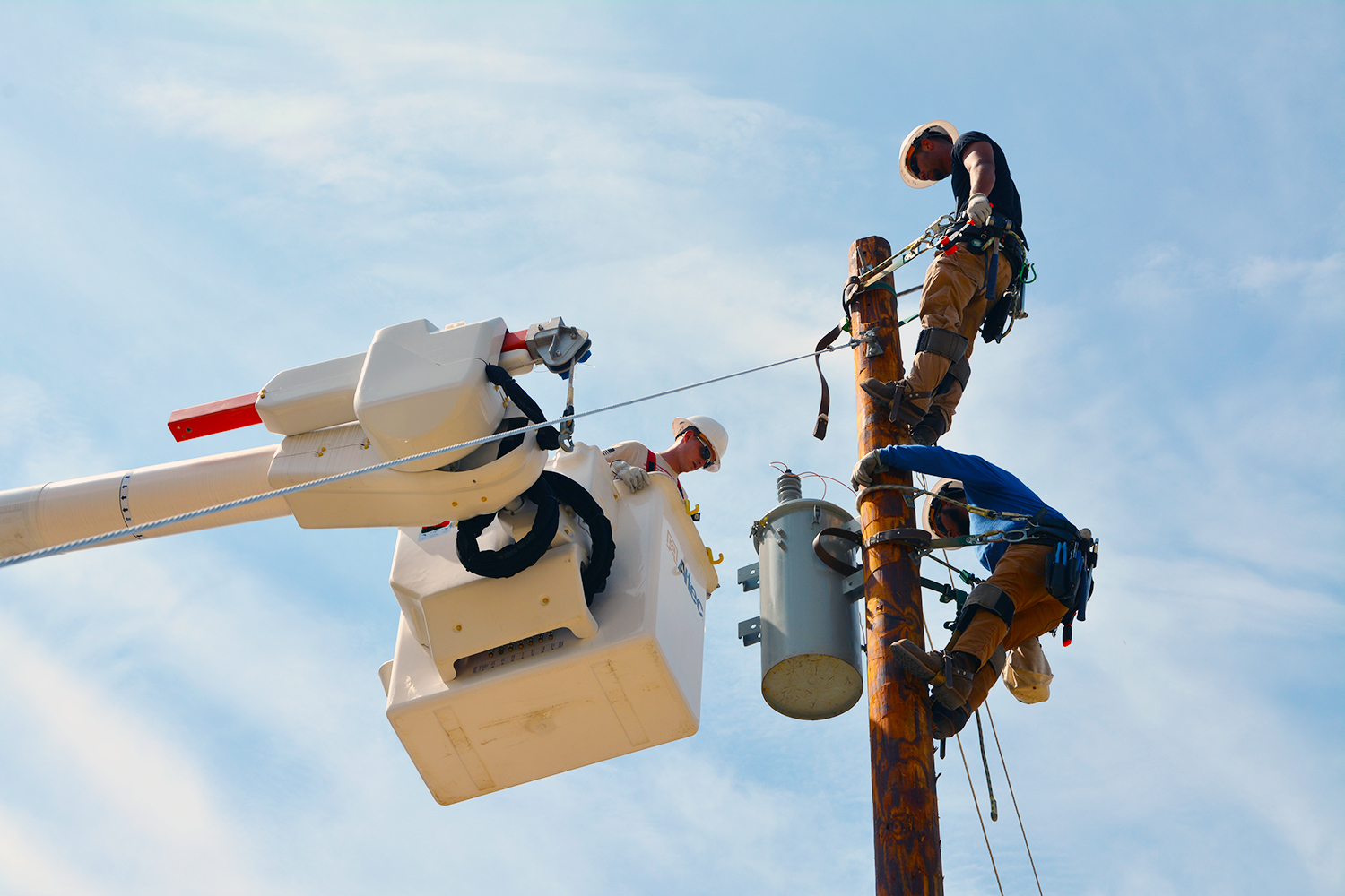Electric lineman students working on a pole top