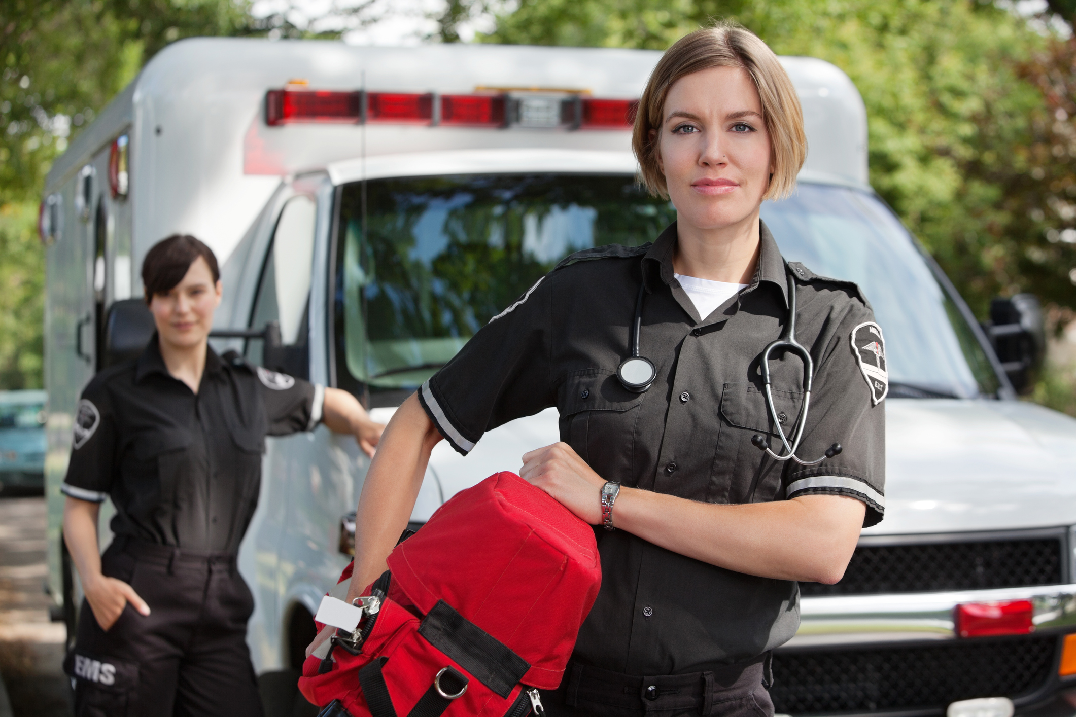 EMT worker with ambulance in the background