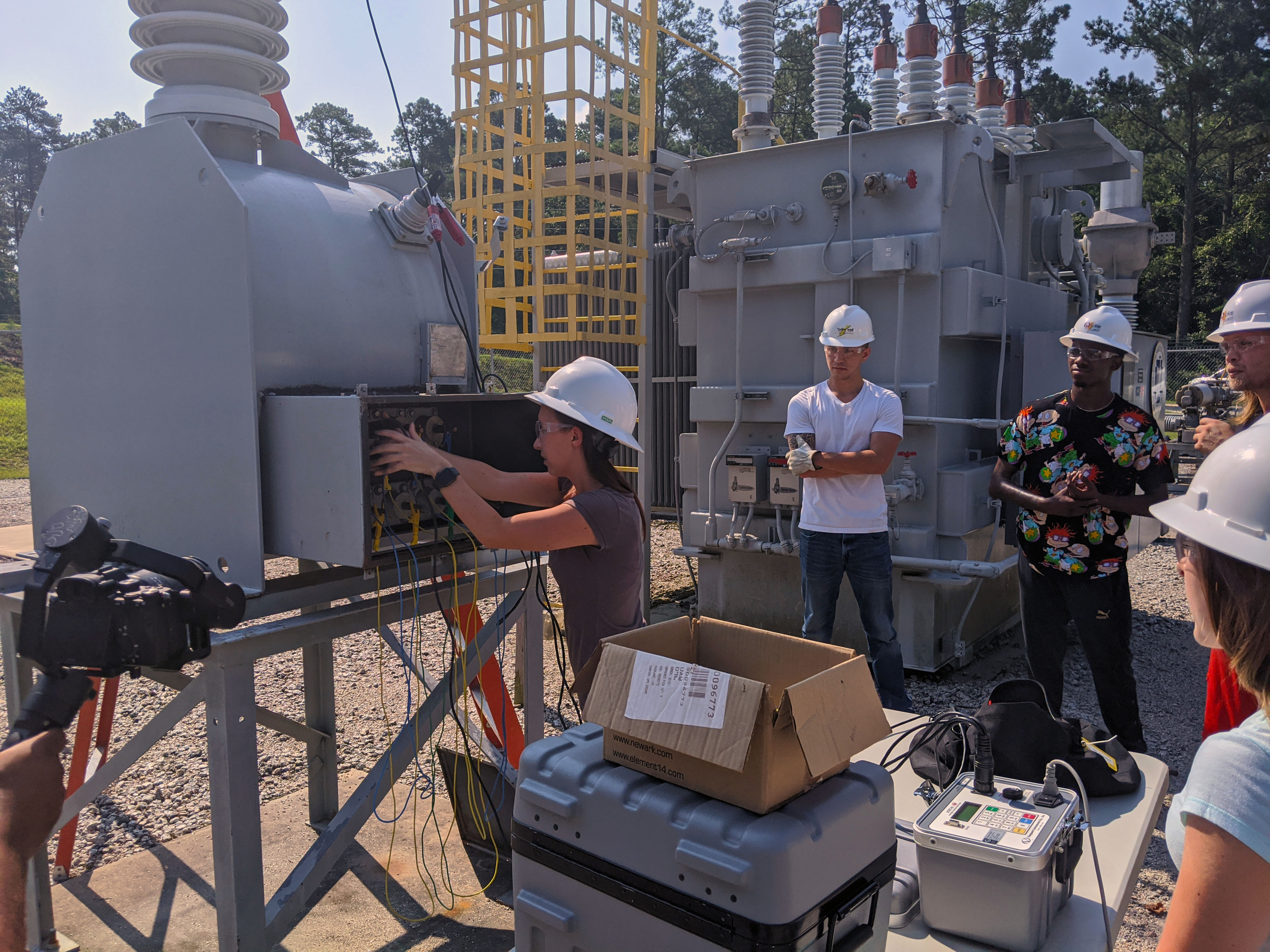 Students stand in the substation and work on testing equipment