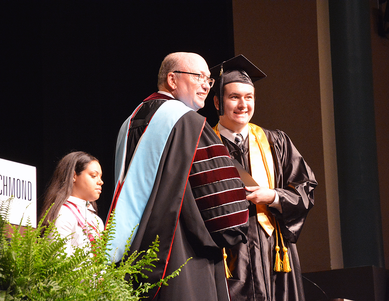 Graduate receives diploma from College President during graduation