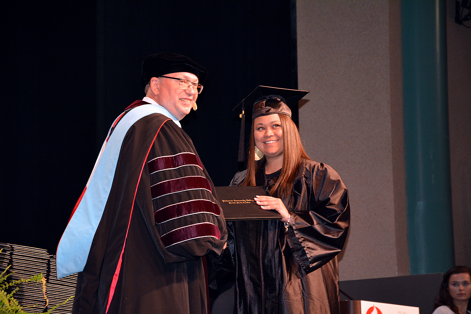 Graduate accepts a diploma and smiles for the camera with Dr. McInnis