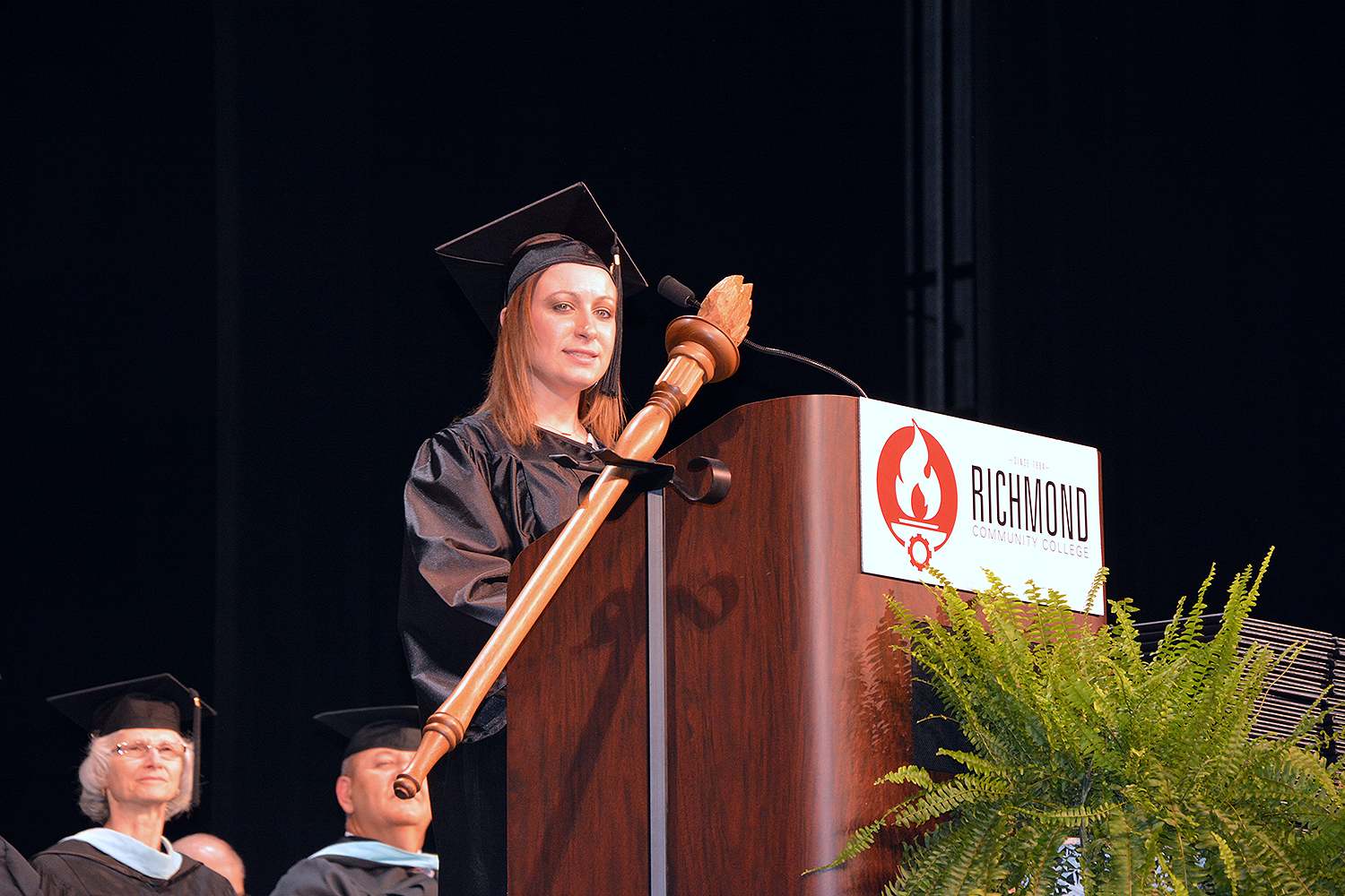 SGA President Nicole Williams stands a podium on stage at graduation