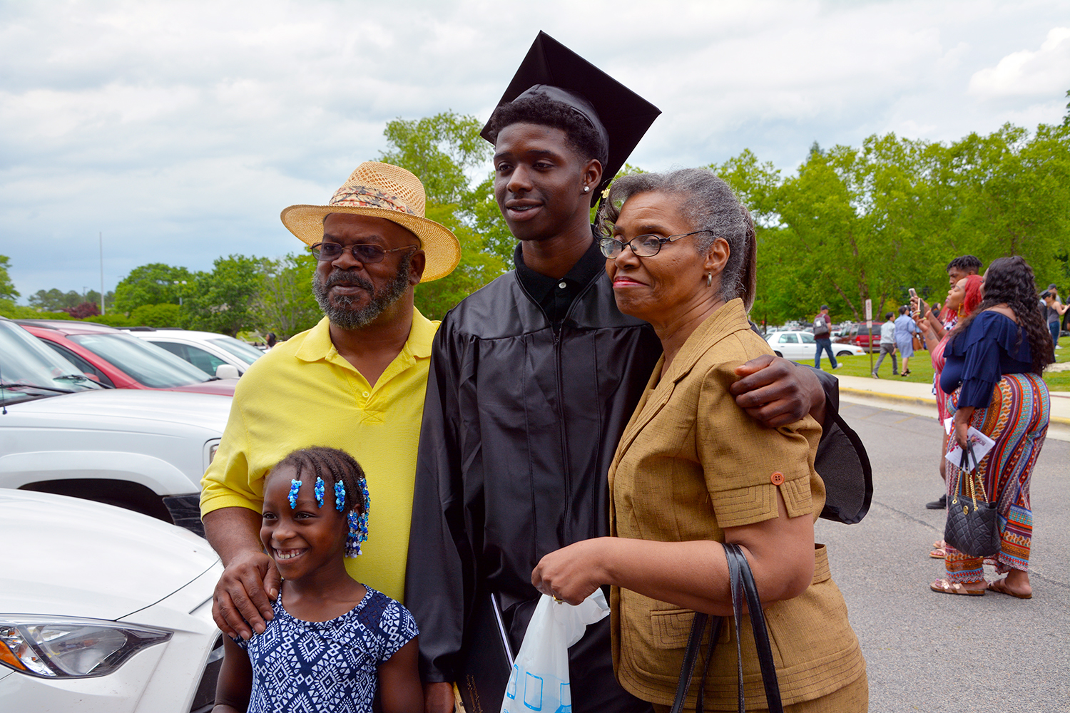 Graduate stands with his family for a photo