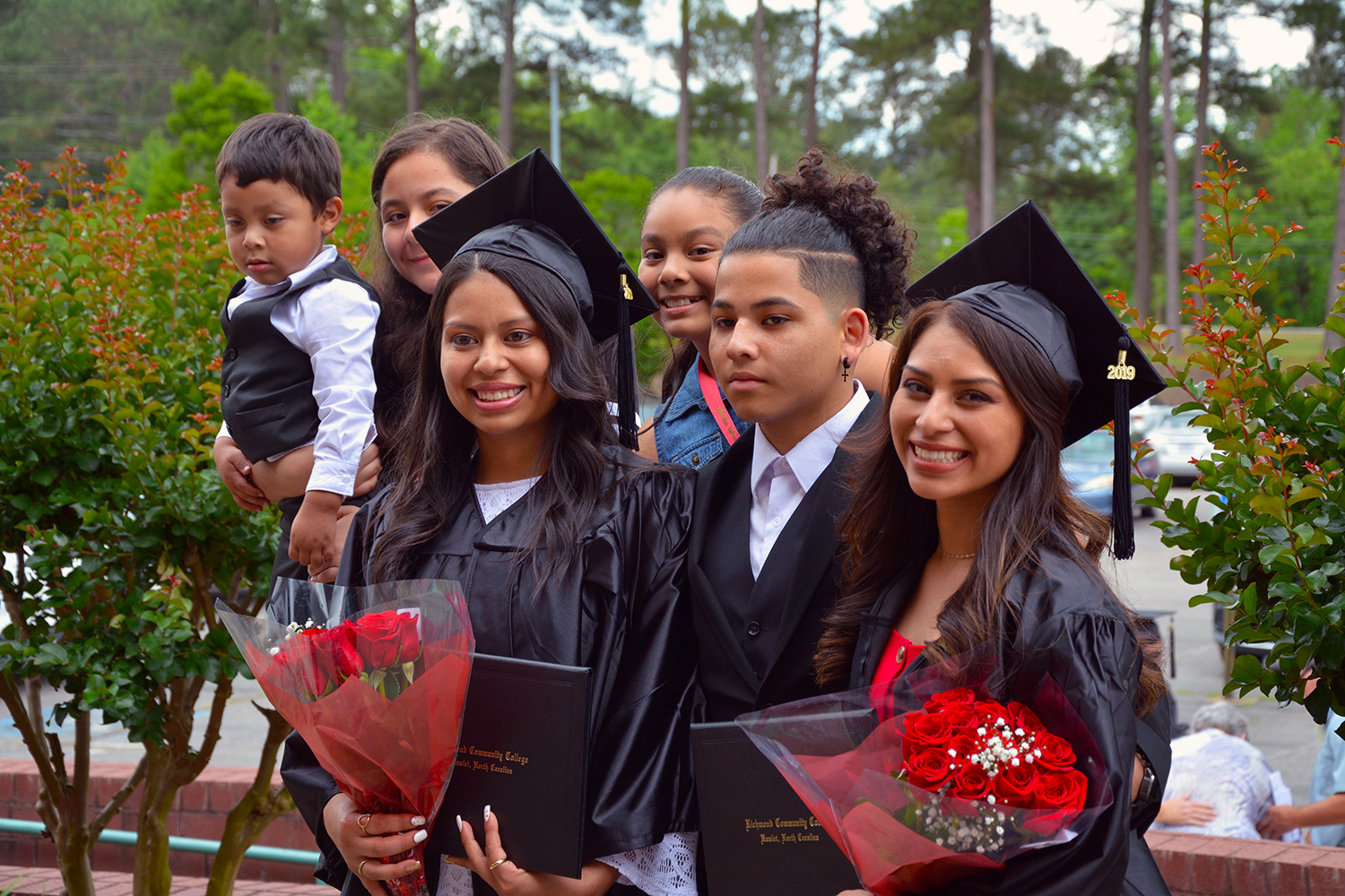 Two graduates stand with family members after the graduation ceremony