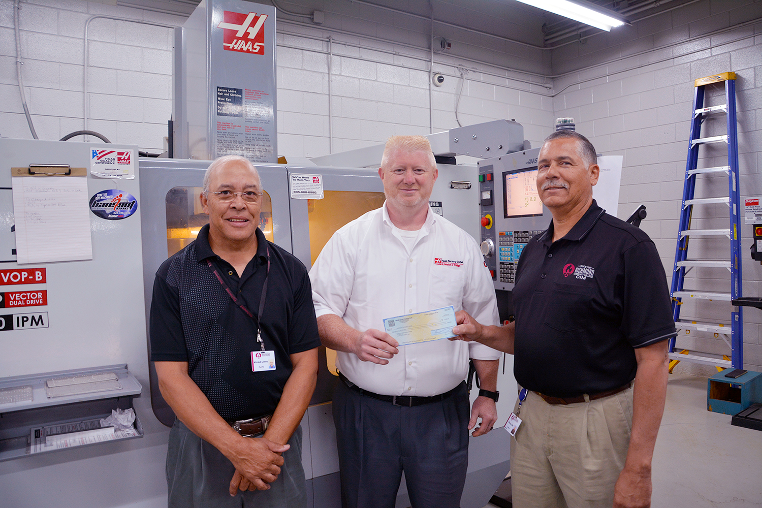 Haas Foundation representative presents check to the two machining instructors