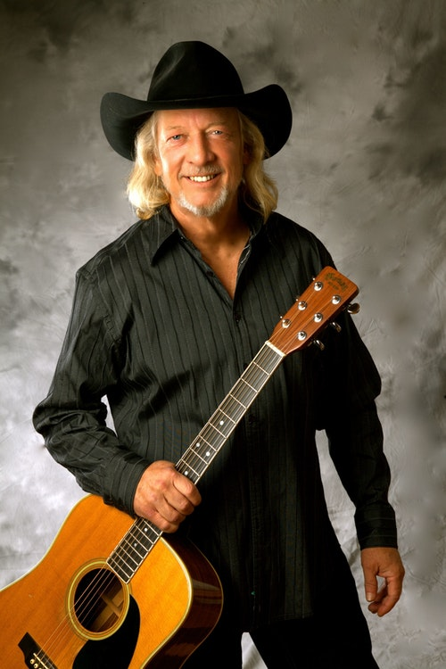 Photo of John Anderson in black cowboy hat holding a guitar