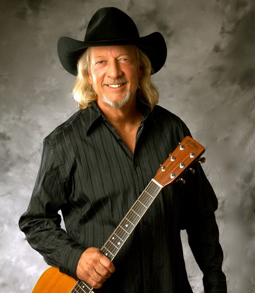 Photo of country music singer John Anderson wearing a black cowboy hat and holding a guitar