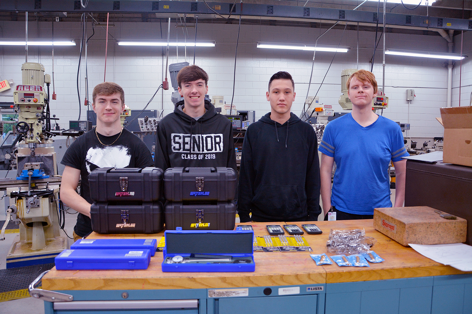 High school students stand with the tool box and tools they received in the machining program.