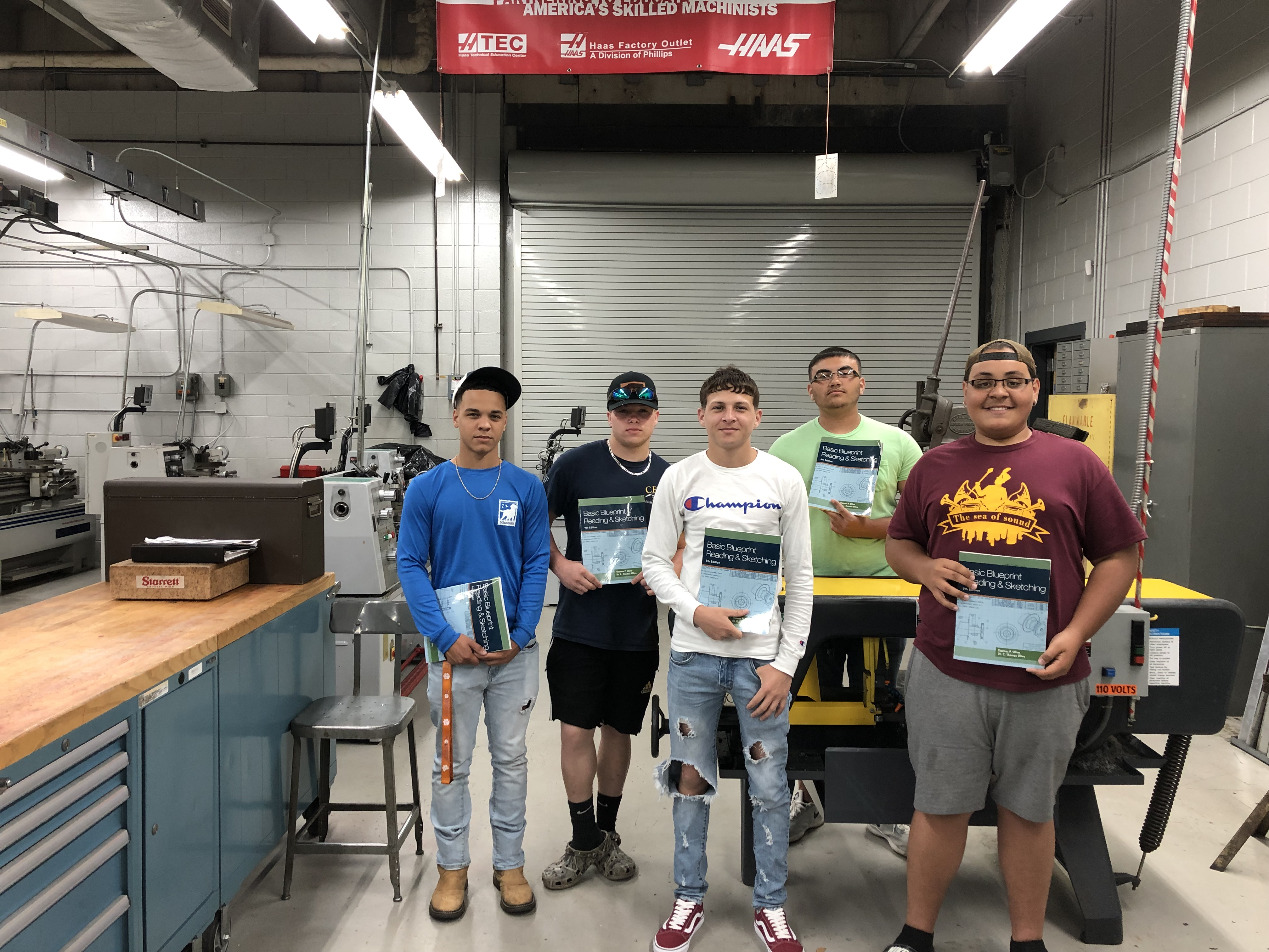 High school students hold the free workbooks they received in the machining program.