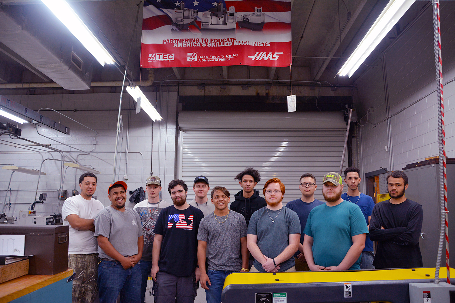 Machining students stand in a group in the machine shop