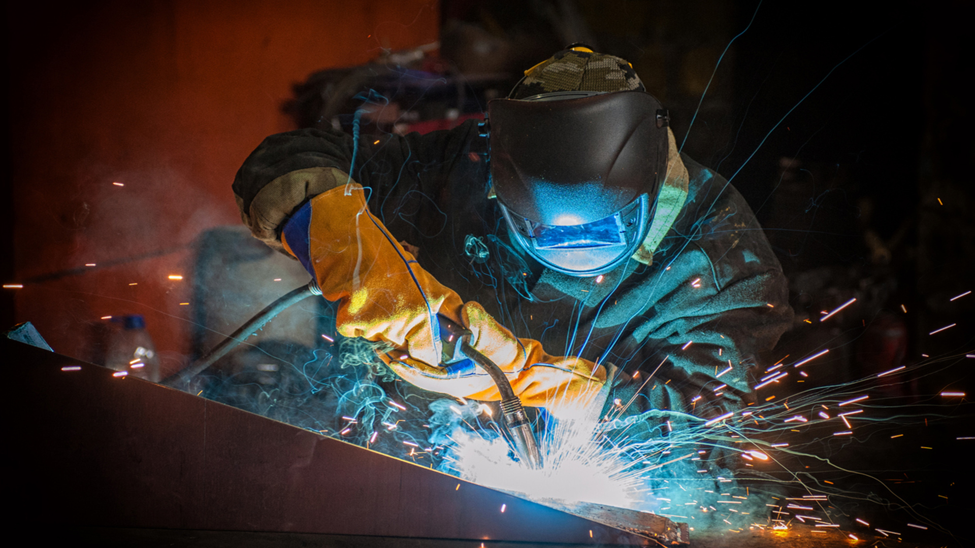 Welder welding with sparks and protective equipment