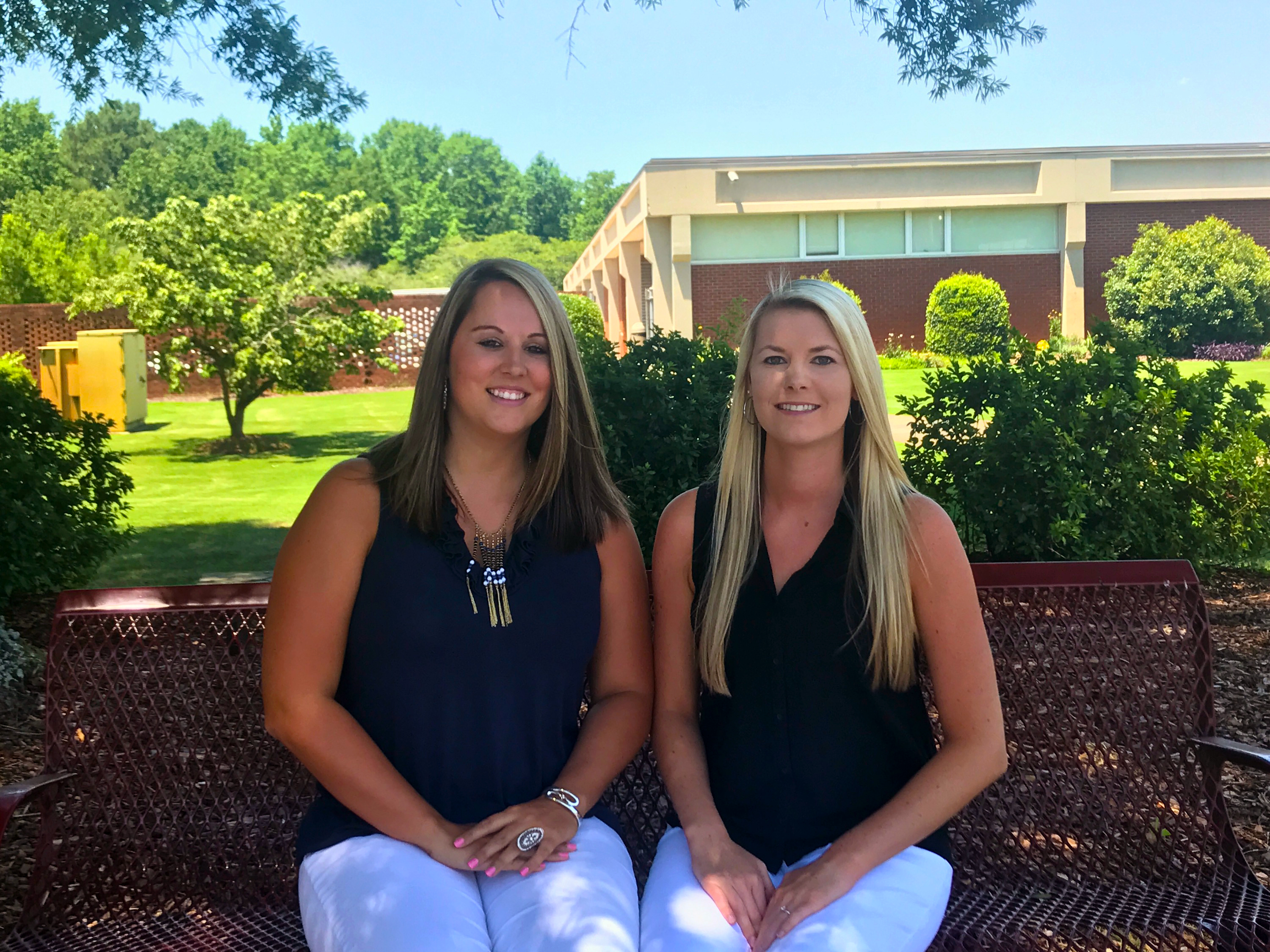 Two office administration graduates sit on a bench on the college campus.