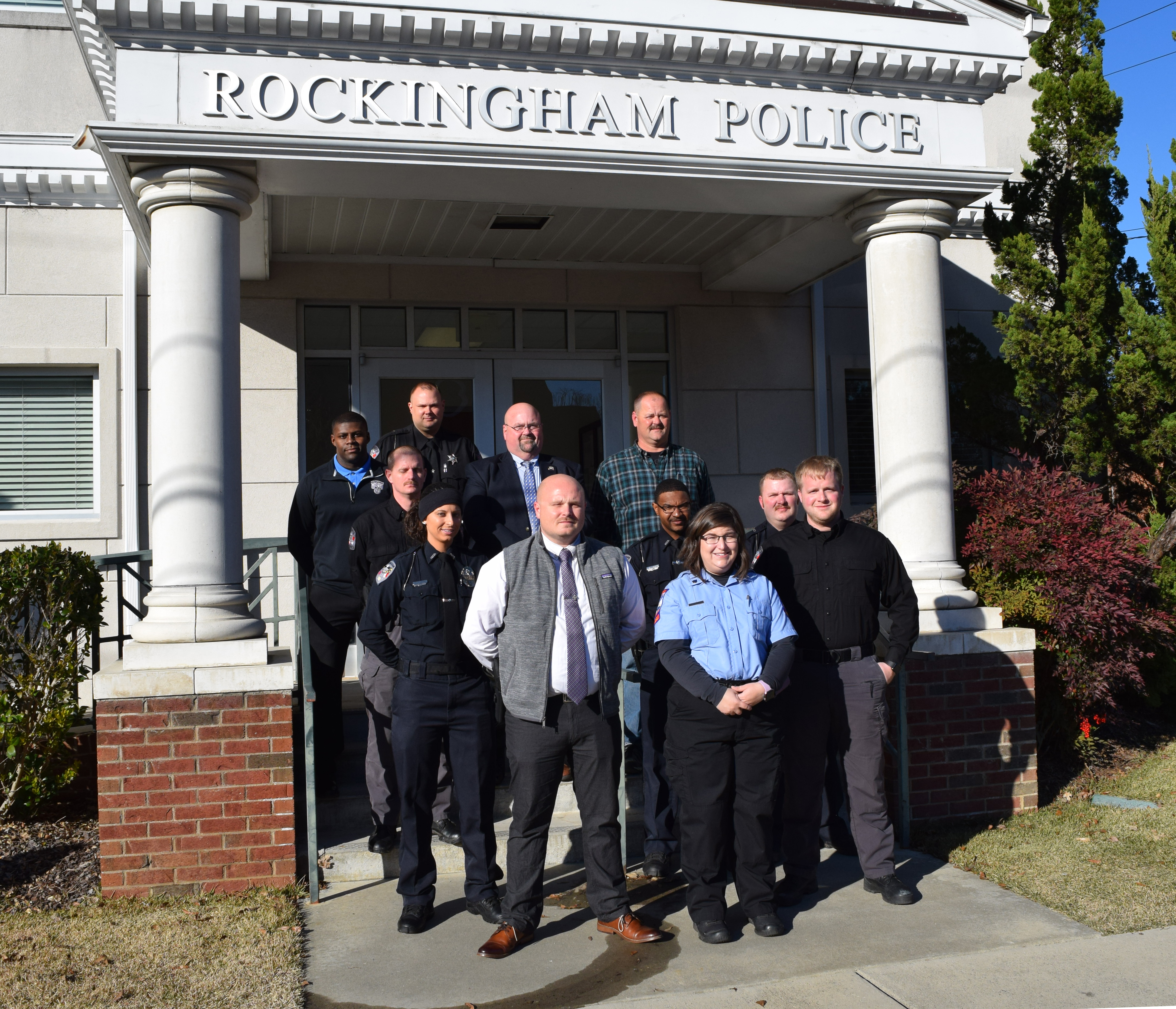 First responders stand on the steps of the Rockingham Police Department.