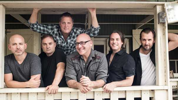 Members of the band Sister Hazel stand on a porch leaning against a railing