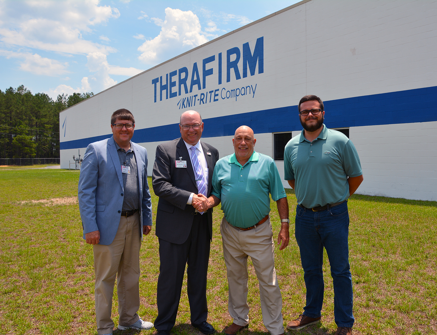Four people stand on the grass in front of the manufacturing plant Therafirm