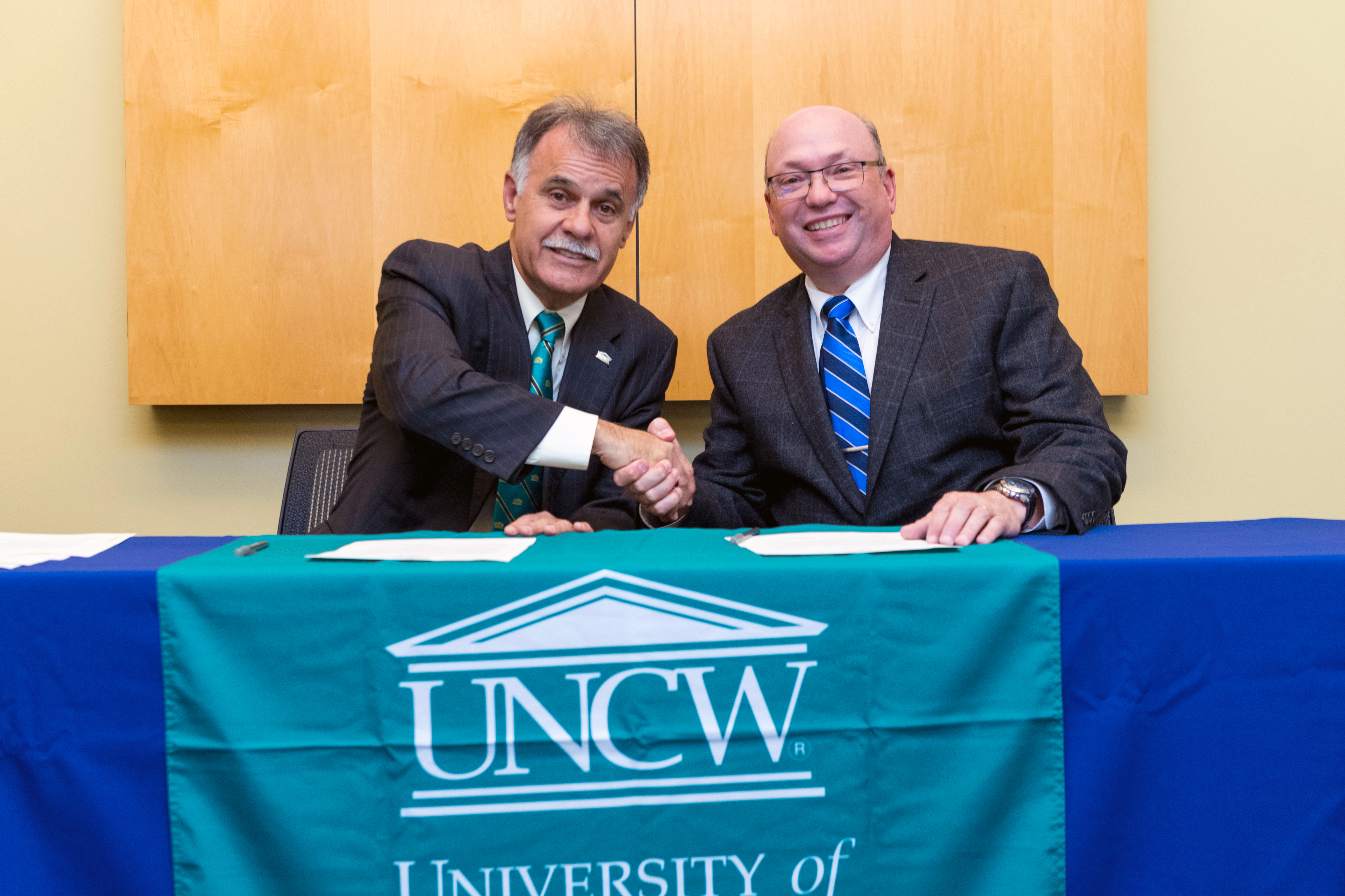 The UNCW Chancellor and the RichmondCC President pose together at a table.