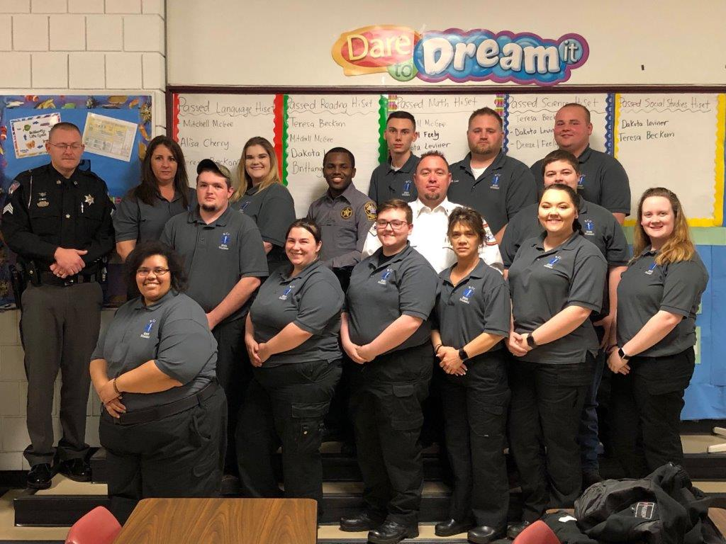 Students who completed the Emergency Medical Technician program pose for a photo in a classroom.