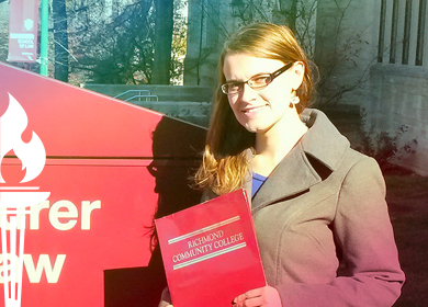 Sarah Doty holding a law book in front of her law school