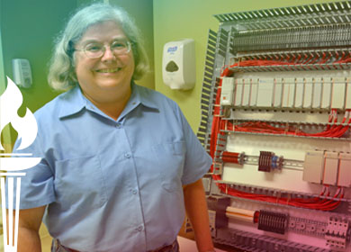 Shirley Koch standing by an electric panel she wired