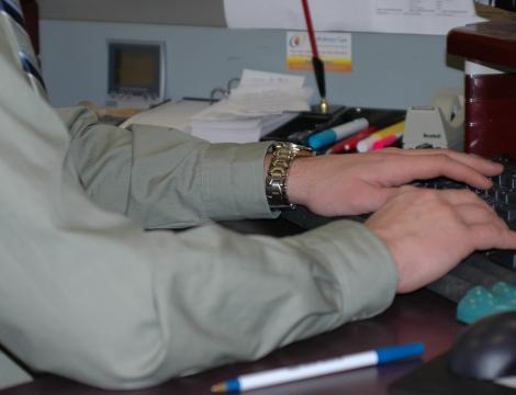man sitting at computer typing