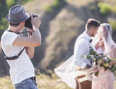 man taking a picture of bride and groom