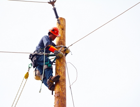 Lineman student climbing up a pole working on a power line