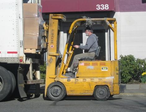 man sitting on a forklift