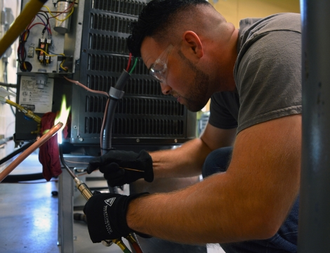 Student brazing a wire on an a/c unit
