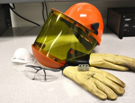 hard hat with shield and safety gloves