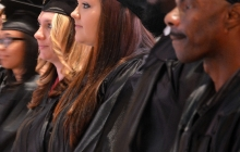 College graduates in cap and gown standing and waiting to receive diplomas
