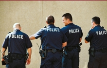 """Group of police officers standing with backs to the camera with the word """"Police"""" emblazoned on backs of shirts"""