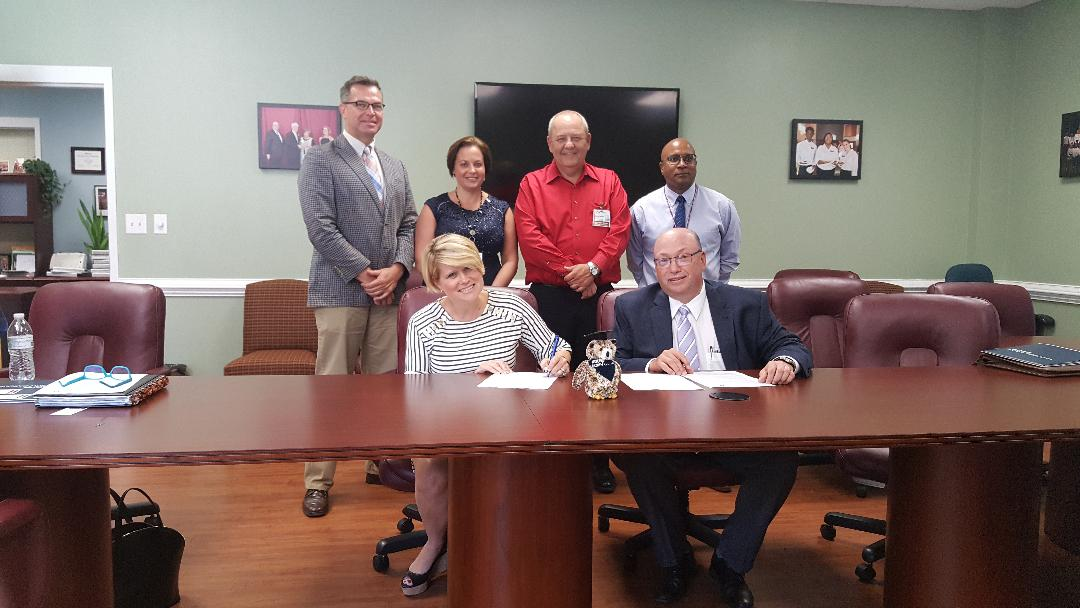 WGU NC Chancellor and RichmondCC President Dr. Dale McInnis sign an agreement while others look on.