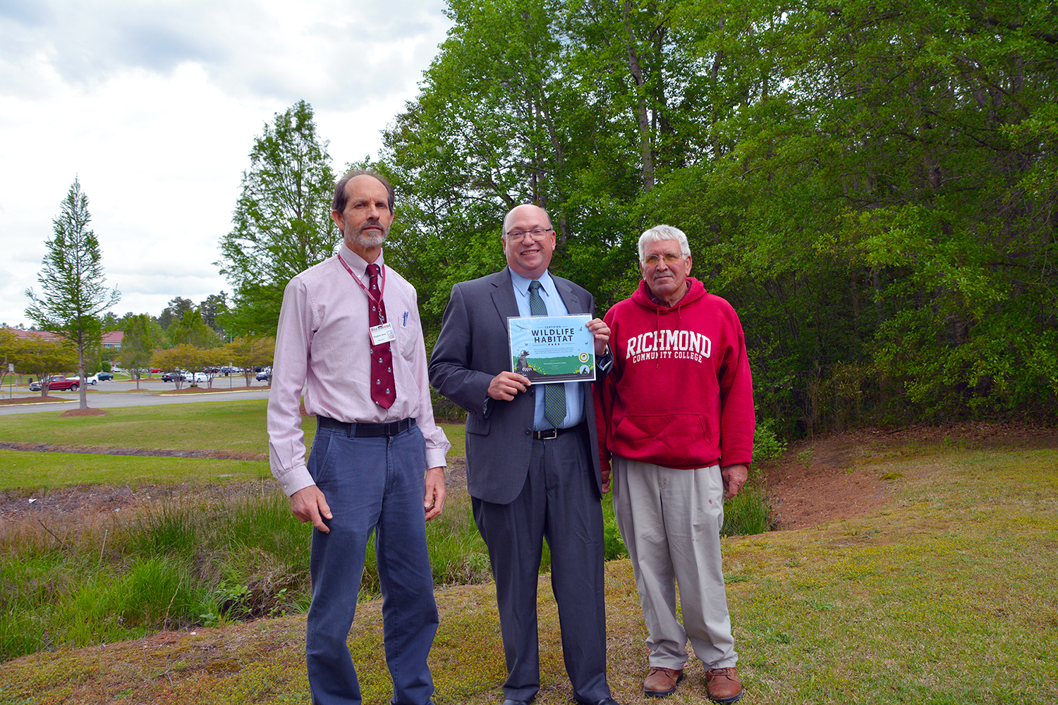 College officials stand near the creek on the campus holding the Wildlife Habitat certification
